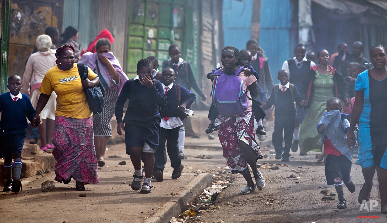 Women and schoolchildren take advantage of a lull in the clashes to run to safety, as police firing tear gas engage protesters throwing rocks in the Kibera slum of Nairobi, Kenya Monday, May 23, 2016. Kenya's police shot, beat and tear gassed opposition demonstrators across the country who tried to gather to call for the electoral commission to be dissolved due to allegations of bias and corruption. (AP Photo/Ben Curtis)