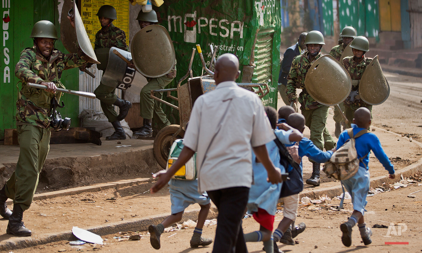 A policeman, left, yells at a man trying to lead schoolchildren to safety, because he was unknowingly about to walk into a hail of rocks thrown by protesters around the corner, as police firing tear gas engage protesters throwing rocks in the Kibera slum of Nairobi, Kenya Monday, May 23, 2016. Kenya's police shot, beat and tear gassed opposition demonstrators across the country who tried to gather to call for the electoral commission to be dissolved due to allegations of bias and corruption. (AP Photo/Ben Curtis)