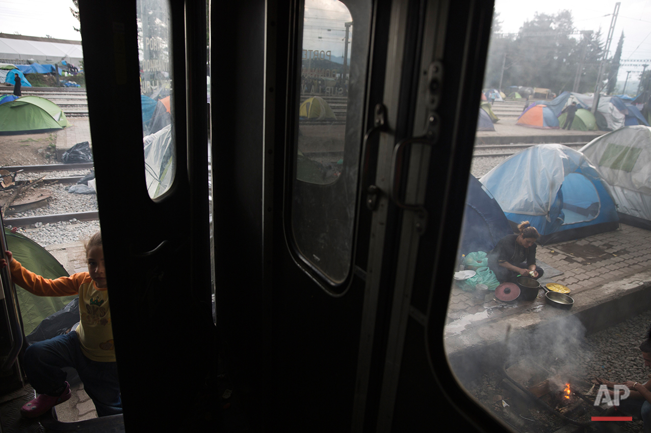 In this Saturday, May 7, 2016 photo, a Syrian girl gets in a train carriage  as a woman cooks food on a makeshift fire in front of tents in the sprawling refugee and migrant tent city in Idomeni, on Greece's northern border with Macedonia. On government orders, Idomeni was cleared this week.  At its peak, it hosted some 14,000 people trapped by Balkan border closures.(AP Photo/Petros Giannakouris)