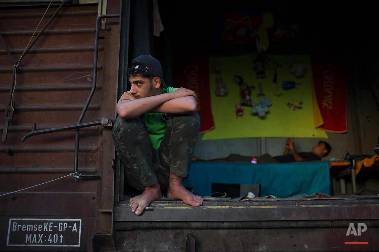 In this Saturday, May 14, 2016 a Syrian young man looks out of a freight car that he lives with his friends  in the sprawling refugee and migrant tent city iN Idomeni, on Greece's northern border with Macedonia. (AP Photo/Petros Giannakouris)