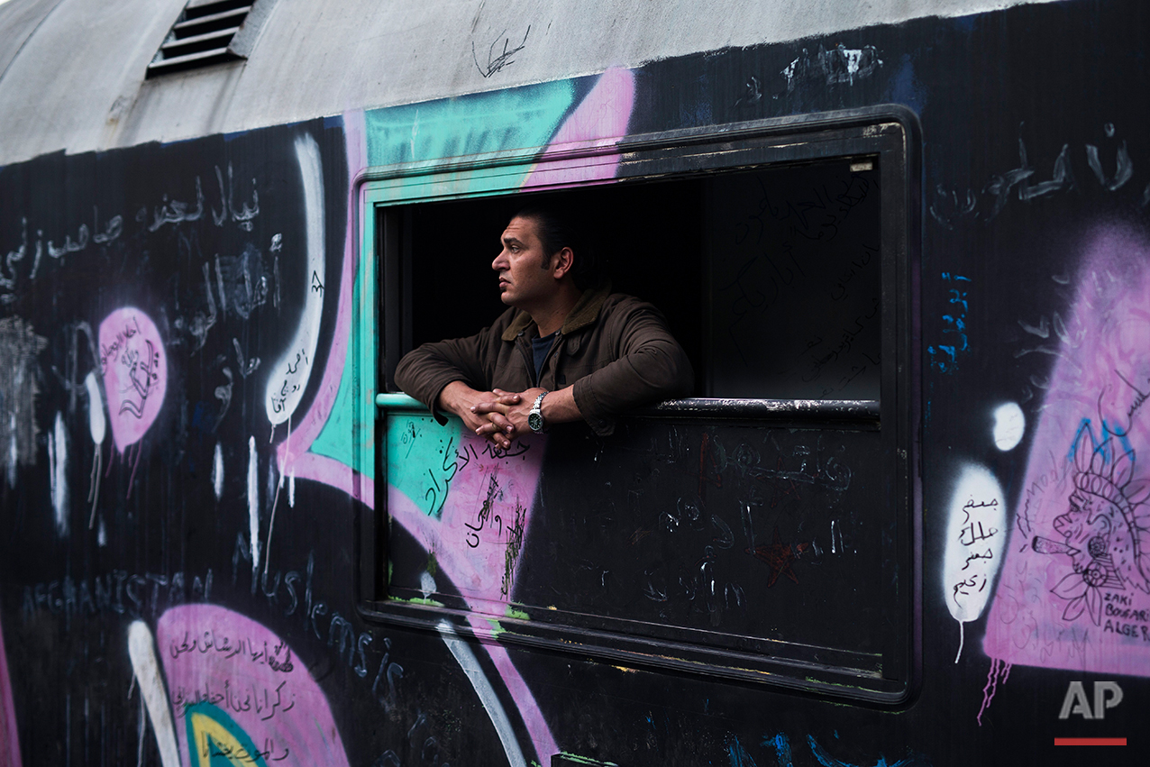 In this Saturday, May 7, 2016 photo, a man looks out of a window of a train that he lives in the sprawling refugee and migrant tent city of Idomeni, on Greece's northern border with Macedonia. After refusing to move for months, refugees camped out at the Greek border were bused to shelters in a police operation this week.(AP Photo/Petros Giannakouris)