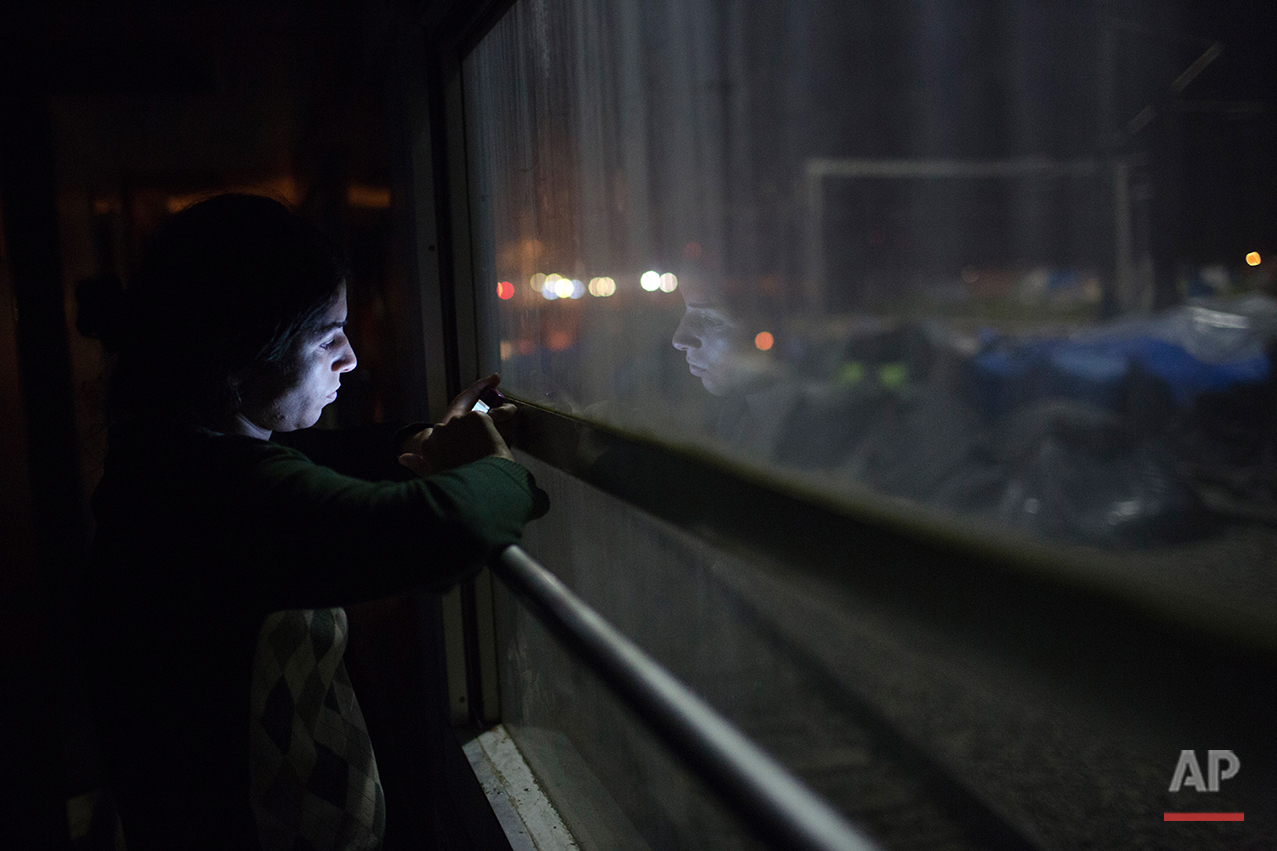 In this Sunday, May 8, 2016 photo, Susdar a 24-year-old Syrian woman look on her mobile phone in the sprawling refugee and migrant tent city if Idomeni, on Greece's northern border with Macedonia. (AP Photo/Petros Giannakouris)