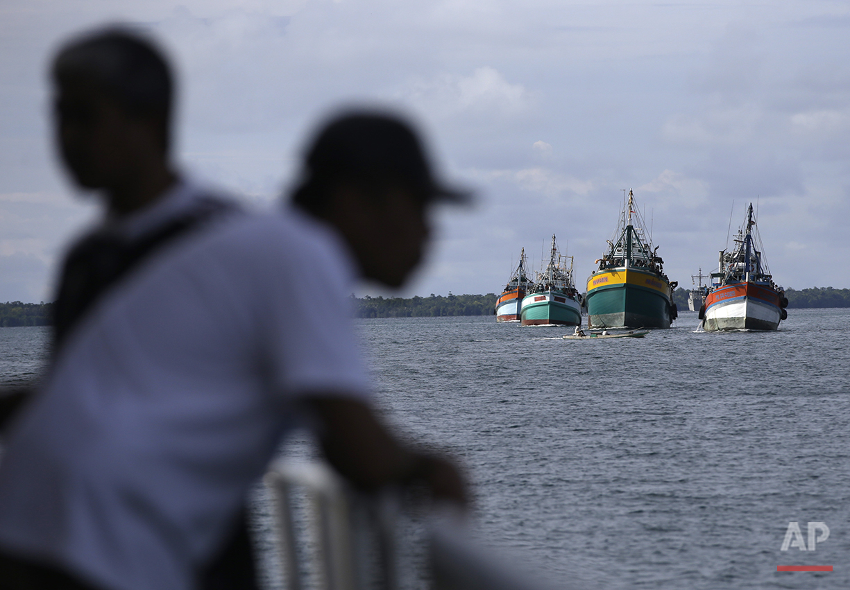 Fishing boats carrying recently rescued fishermen sail toward the town of Tual, Indonesia, Saturday, April 4, 2015. The rescued fishermen were among hundreds of migrant workers revealed in an Associated Press investigation to have been lured or tricked into leaving their countries and were brought to Indonesia to be forced to catch seafood. (AP Photo/Dita Alangkara)