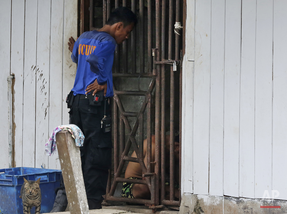In this Nov. 2014, photo, a security guard talks to detainees inside a cell at the compound of a fishing company in Benjina, Indonesia. The imprisoned men were considered slaves who might run away. They said they lived on a few bites of rice and curry a day in a space barely big enough to lie down, stuck until the next trawler forces them back to sea. In its first report on trafficking around the world, the U.S. criticized Thailand as a hub for labor abuse. Yet 14 years later, seafood caught by slaves on Thai boats is still slipping into the supply chains of major American stores and supermarkets. (AP Photo/Dita Alangkara)