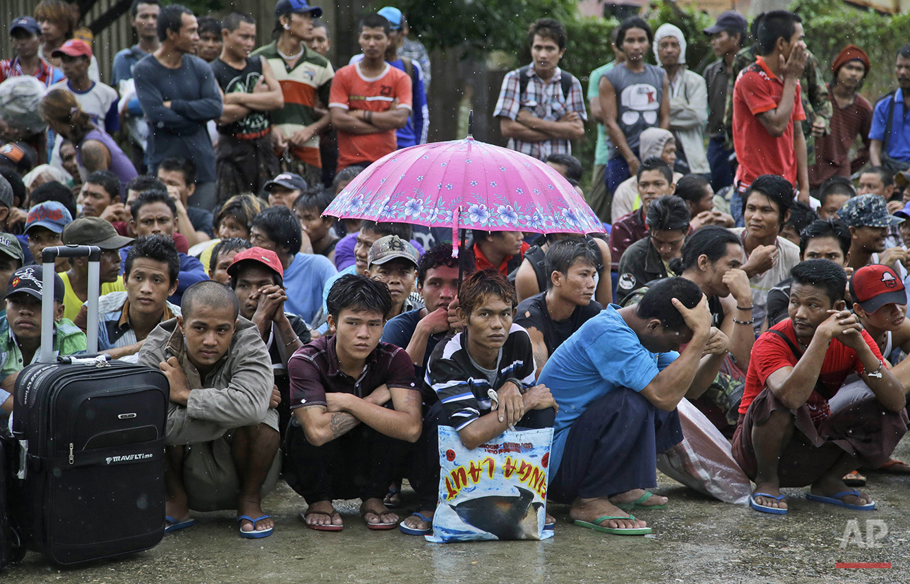 Burmese fishermen wait for their departure to leave the compound of Pusaka Benjina Resources fishing company in Benjina, Aru Islands, Indonesia, Friday, April 3, 2015. Hundreds of foreign fishermen on Friday rushed at the chance to be rescued from the isolated island where an Associated Press report revealed slavery runs rampant in the industry. Indonesian officials investigating abuses offered to take them out of concern for the men's safety. (AP Photo/Dita Alangkara)