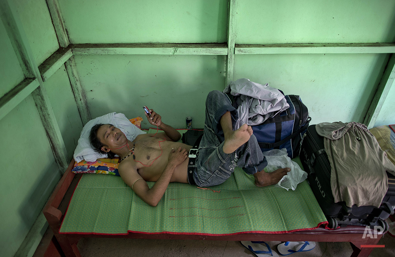In this May 15, 2015, photo, Myint Naing, a former slave fisherman who spent more than two decades in Indonesia after being enslaved on Thai fishing boats, rests at a government hostel in Yangon, Myanmar after returning to his home country the day before. Myint, 40, is among hundreds of former slave fishermen who returned to Myanmar following an Associated Press investigation into the use of forced labor in Southeast Asia's seafood industry. (AP Photo/Gemunu Amarasinghe)