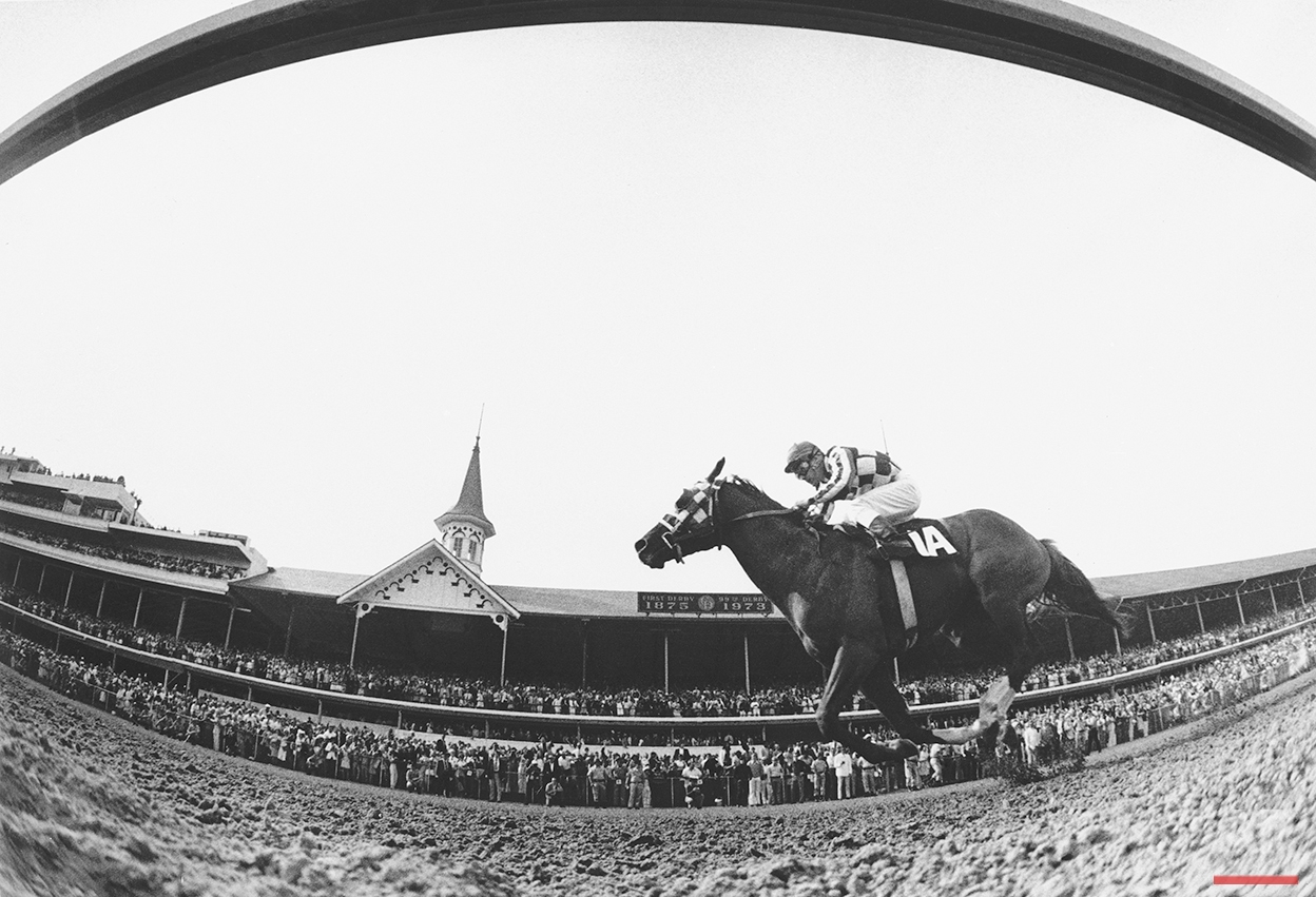 This is a fish-eye lens view of Secretariat, ridden by Ron Turcotte, thundering past the packed clubhouse at Churchill Downs, Louisville, Ky., to win the 1973 Kentucky Derby May 5, 1973. (AP Photo)