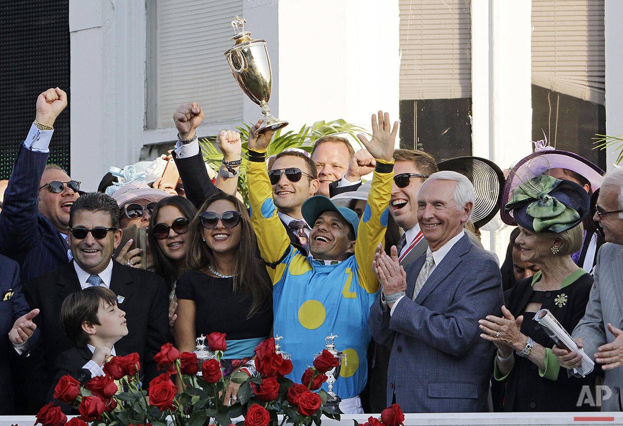 Victor Espinoza celebrates after riding American Pharoah to victory in the 141st running of the Kentucky Derby horse race at Churchill Downs Saturday, May 2, 2015, in Louisville, Ky. (AP Photo/Garry Jones)