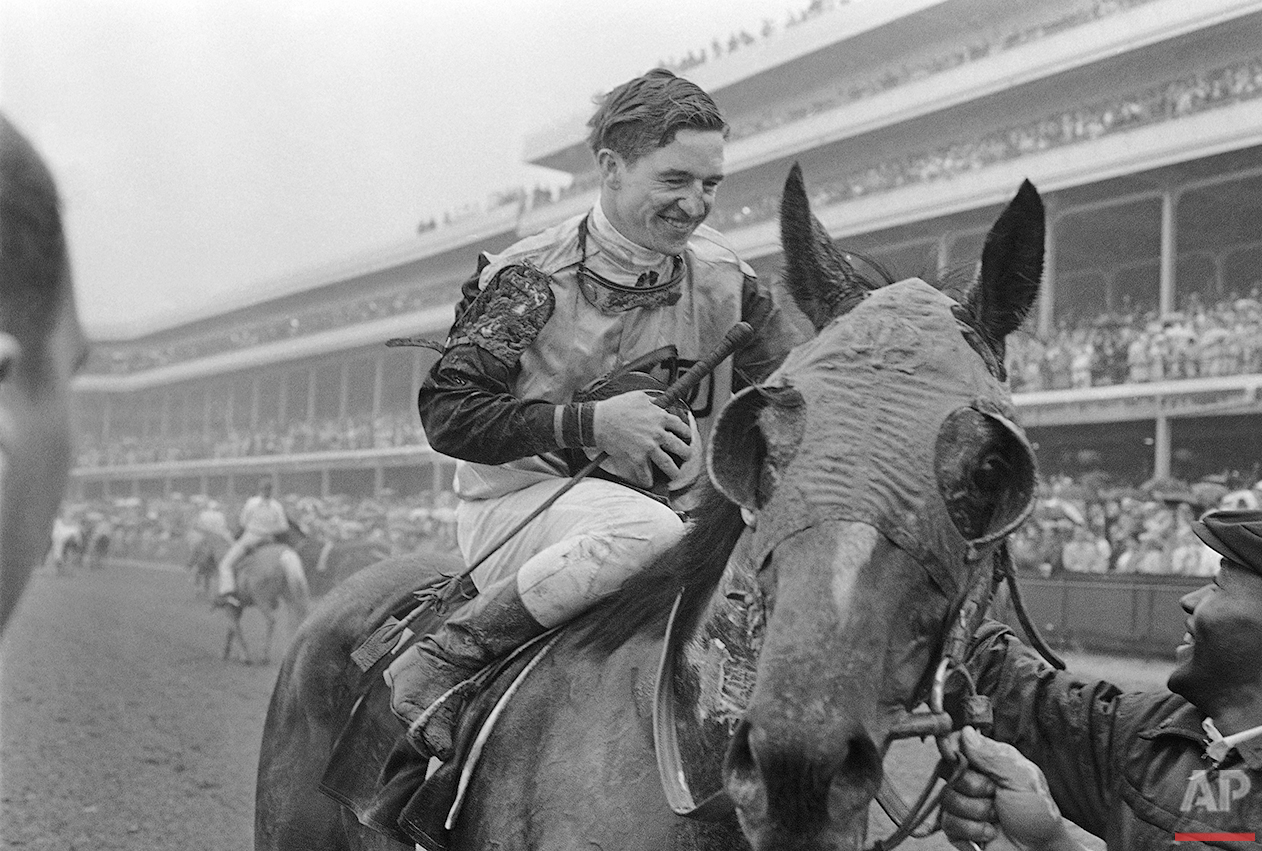 Some of the mud from rain-soaked Churchill Downs track clings to faces of Kentucky Derby winner Proud Clarion and his happy mount Bob Ussery as they enter the winners circle, May 6, 1967 in Louisville, Kentucky after the race. (AP Photo)