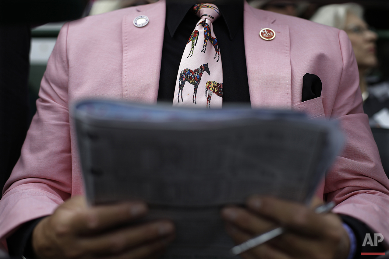 Phil Shewciw reads a racing program before the running of the 139th Kentucky Oaks at Churchill Downs, Friday, May 3, 2013, in Louisville, Ky. (AP Photo/David Goldman)