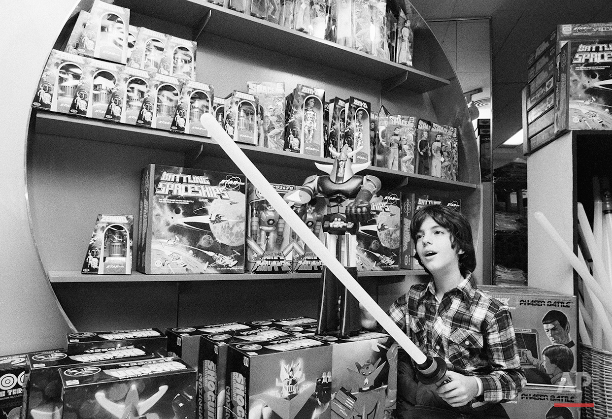 "Haik Gazarian, 11, from Caracas, Venezuela, who now lives in New York, tries to cut a toy ""Force Wand,""  an illuminated toy sword inspired by the film ""Stars Wars,"" during the visit to the toy department store, on Wednesday Dec. 22, 1977. In the background are a number of other toys inspired by the current popularity of ""Space Opera"" type films. (AP Photo/Marty Lederhandler)"