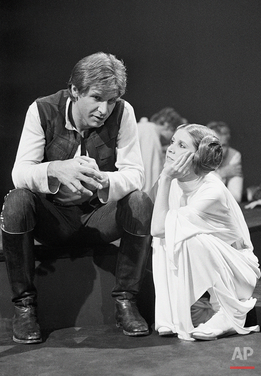"Harrison Ford, as Han Solo of ""Star Wars"" fame chats with Carrie Fisher Nov. 13, 1978 during a break in the filming of the CBS-TV special ""The Star Wars Holiday."" Ford says he leaves the singing in the special to Carrie, who is the daughter of Eddie Fisher and Debbie Reynolds. The film will also feature many special effects not seen on the original movie. (AP Photo/George Brich )"