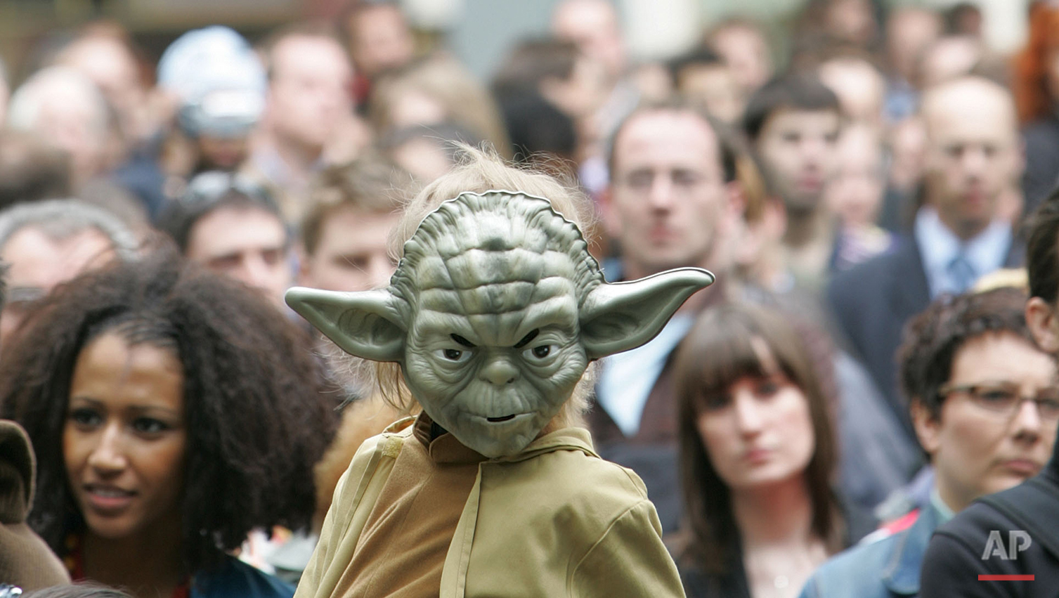 A young boy dressed as the Star Wars character 'Yoda' sits on the shoulders of a man as he watches events in Leicester Square in London and joins in with the premier launch of the film Star Wars Episode III Revenge of the Sith,  Monday May 16, 2005.  The film by American Director George Lucas is the last in the Star Wars series. (AP Photo/Alastair Grant)