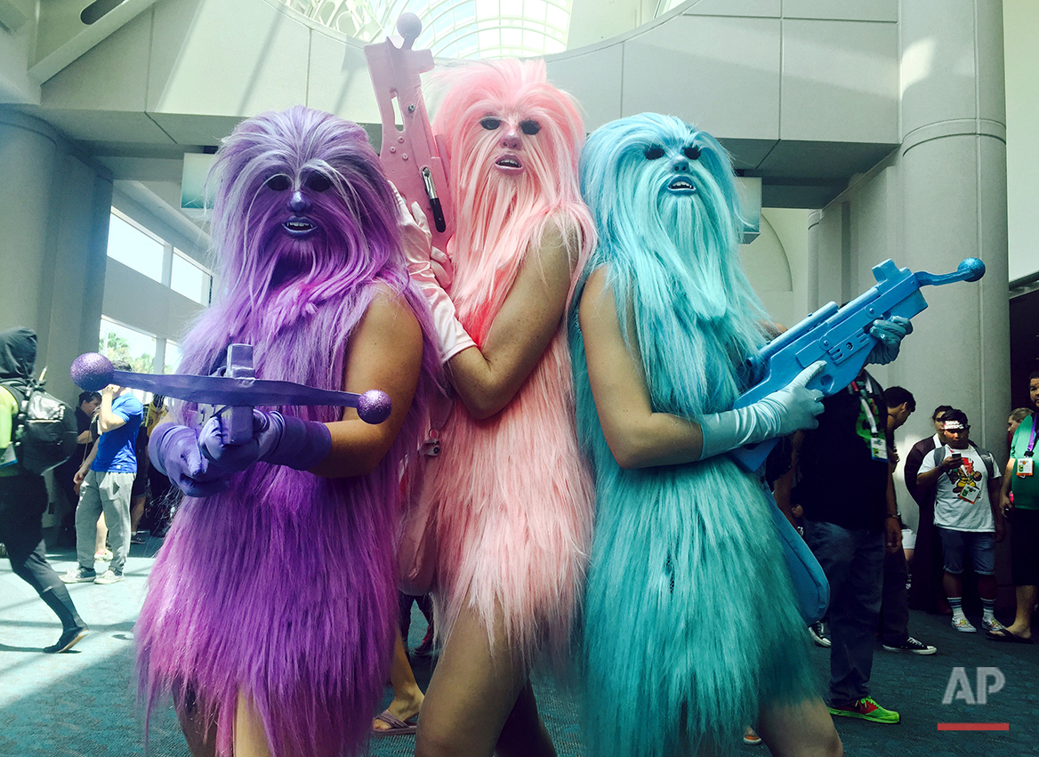 "In this July 10, 2015 photo, fans dressed as ""Chewie's Angels"" attend day 2 of Comic-Con International, in San Diego, Calif. Star Wars"" inspires curiously personal reactions. It drives some people to don Wookie costumes and others to curse an entire industry as infantile. Since the 1977 debut of ""A New Hope,"" it's become a generational rite of passage not just to experience the saga, but to form one's relationship with movies around it, whether in happy lockstep or rebel opposition. (Photo by Chelsea Vicari/Invision/AP)"