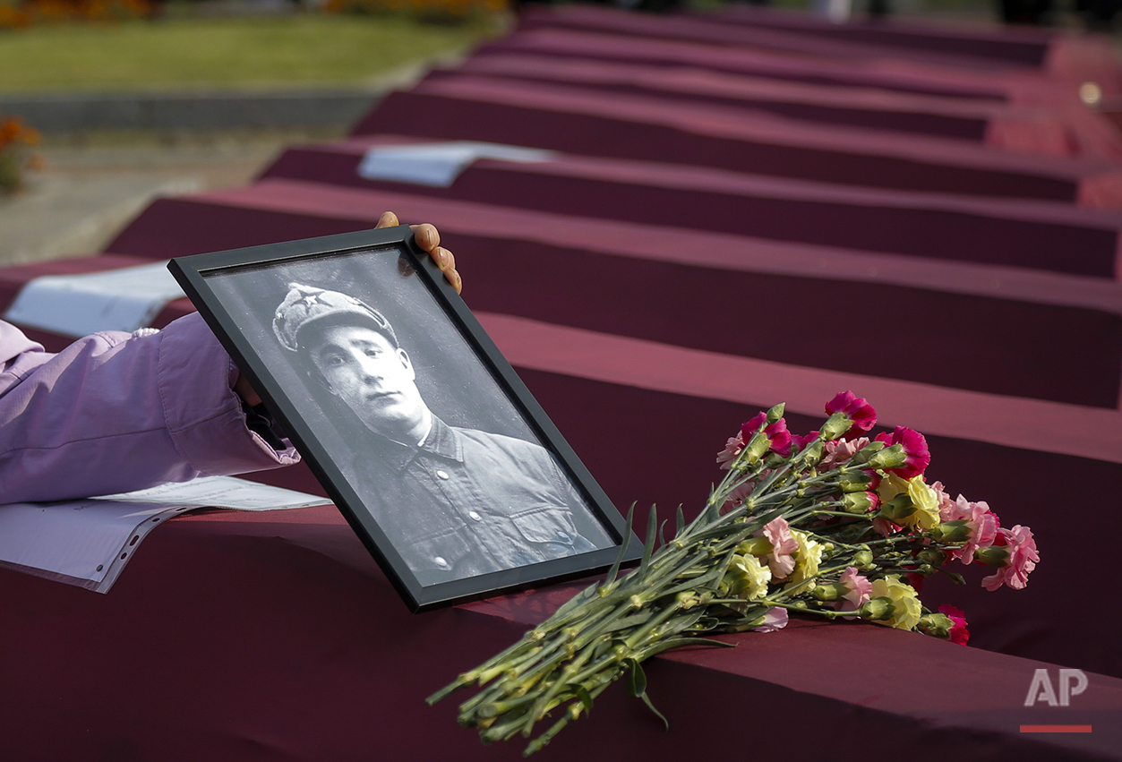 In this photo taken on Friday, Sept. 18, 2015, Zoya Izotova, niece of Ivan Shagichev, Soviet soldier killed in 1941, holds a portrait of her uncle at a coffin with his remains during a burial ceremony in a memorial cemetery at Nevsky Pyatachok near Kirovsk, Russia. Nevsky Pyatachok, an area about 50 kilometers (30 miles) southeast of St. Petersburg, has proved especially fertile ground. As many as 200,000 Soviet soldiers were killed here between September 1941 and May 1943 in fighting to break the Nazi siege of the city, which was then called Leningrad. (AP Photo/Dmitri Lovetsky)