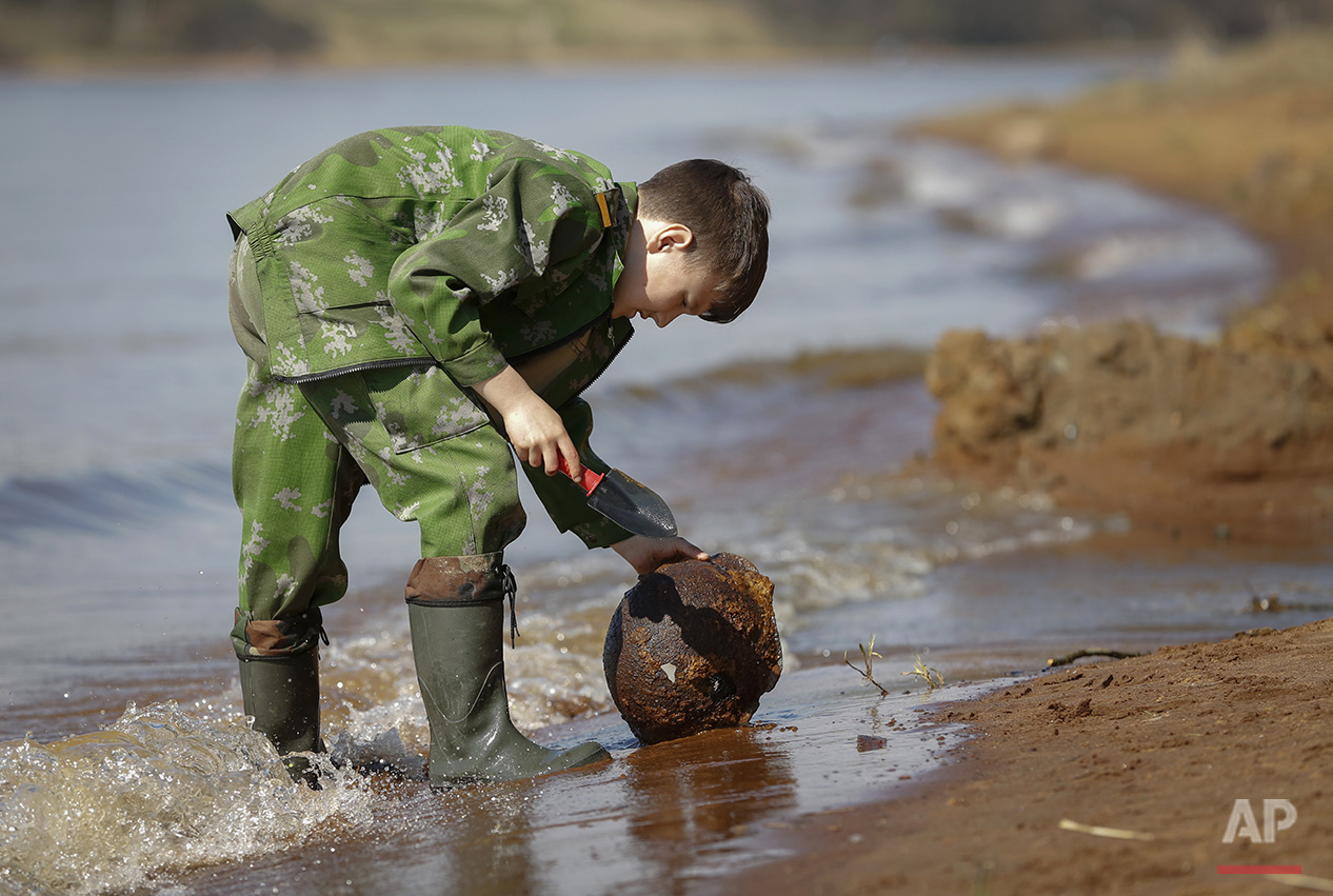 In this photo taken on Monday, May  2, 2016, Gosha, 10-year-old son of a member of a volunteer group searching for the remains of Soviet soldiers killed during WWII, cleans an uncovered WWII Soviet helmet at Nevsky Pyatachok near Kirovsk,  Russia. Nevsky Pyatachok, an area about 50 kilometers (30 miles) southeast of St. Petersburg, has proved especially fertile ground. As many as 200,000 Soviet soldiers were killed here between September 1941 and May 1943 in fighting to break the Nazi siege of the city, which was then called Leningrad.  (AP Photo/Dmitri Lovetsky)