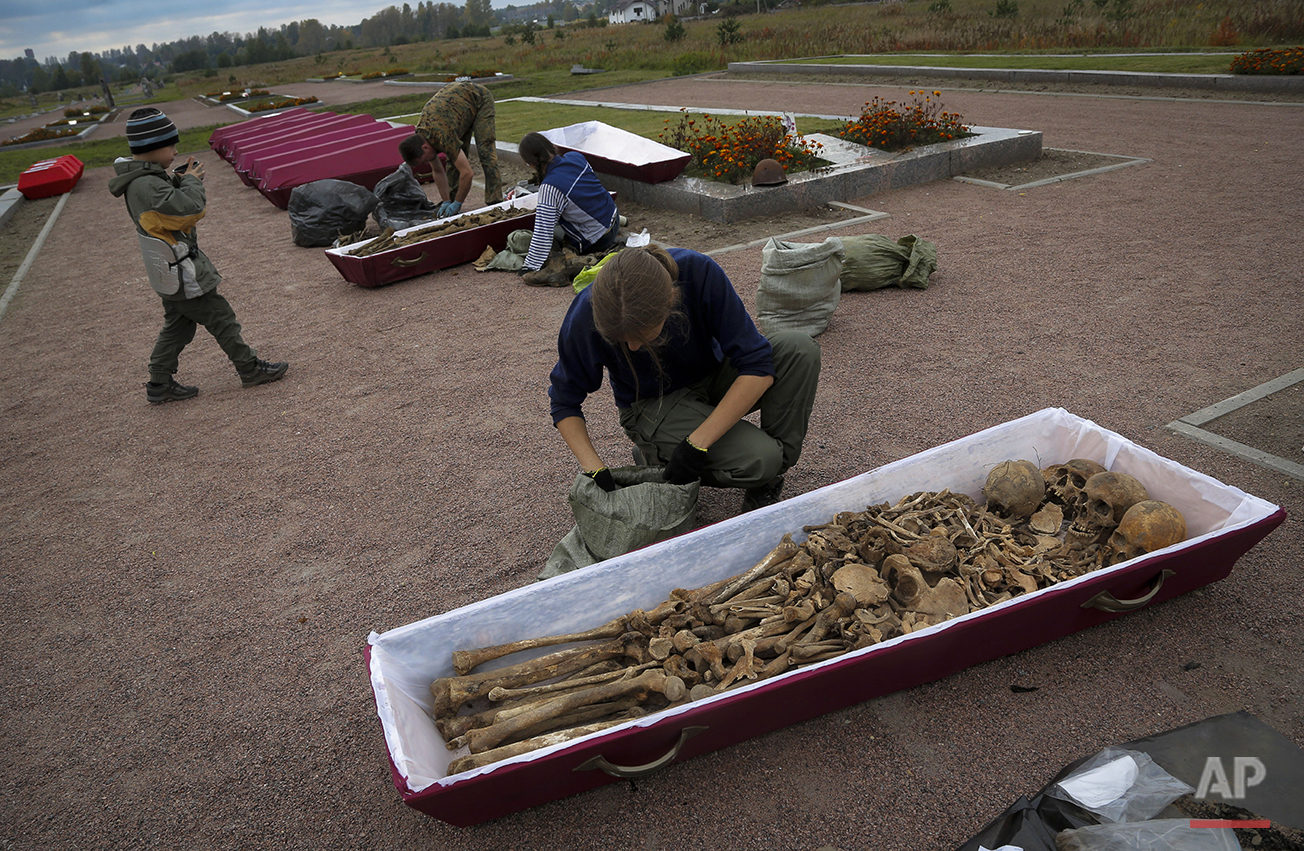 In this photo taken on Thursday, Sept.  17, 2015, members of a volunteer group searching for the remains of Soviet soldiers killed during WWII, put remains in coffins during preparation for burial in a memorial cemetery at Nevsky Pyatachok near Kirovsk, Russia. Nevsky Pyatachok, an area about 50 kilometers (30 miles) southeast of St. Petersburg, has proved especially fertile ground. As many as 200,000 Soviet soldiers were killed here between September 1941 and May 1943 in fighting to break the Nazi siege of the city, which was then called Leningrad.  (AP Photo/Dmitri Lovetsky)
