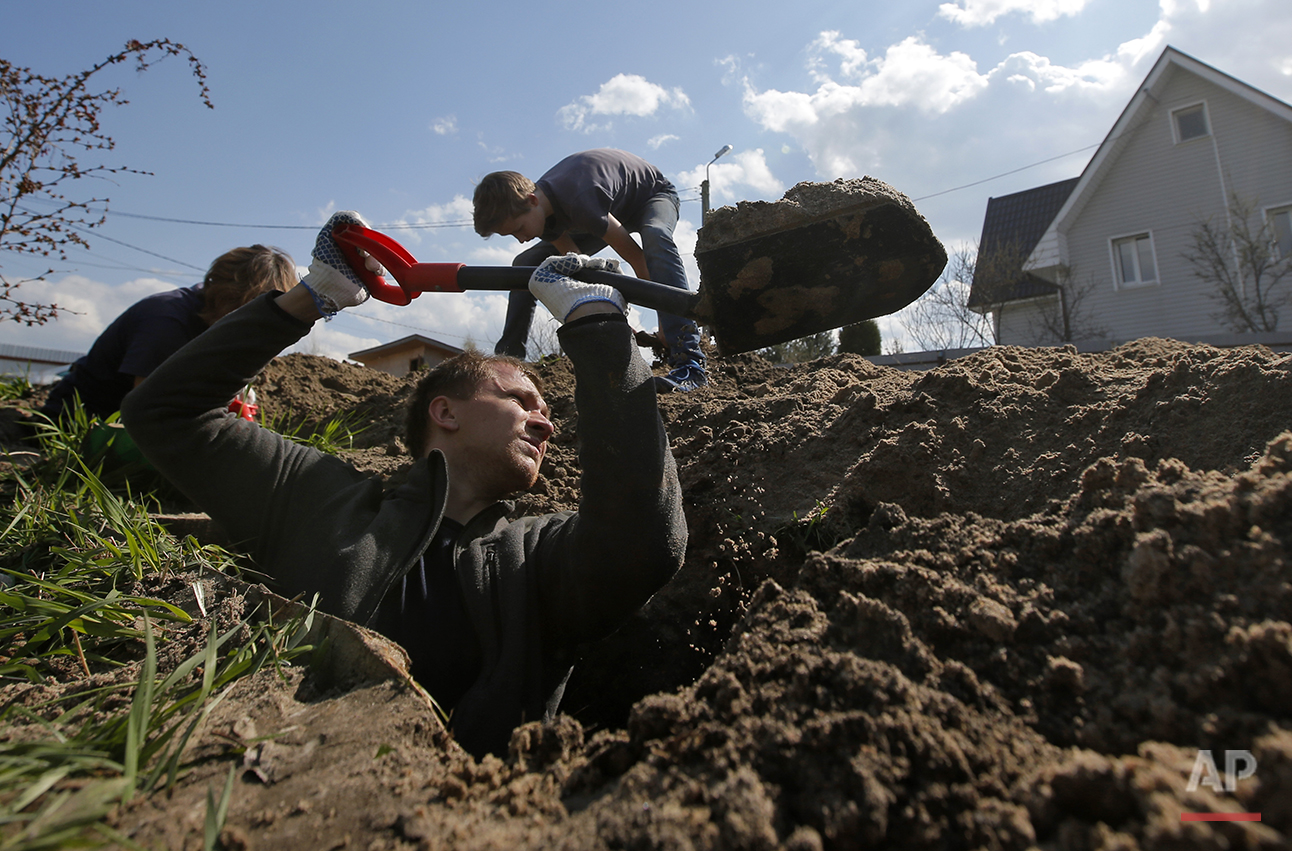 In this photo taken on Tuesday, May  3, 2016, members of a volunteer group searching for the remains of Soviet soldiers killed during WWII, dig to uncover remains of  Soviet soldiers at the yard of a private house at Nevsky Pyatachok near Kirovsk,  Russia. Nevsky Pyatachok, an area about 50 kilometers (30 miles) southeast of St. Petersburg, has proved especially fertile ground. As many as 200,000 Soviet soldiers were killed here between September 1941 and May 1943 in fighting to break the Nazi siege of the city, which was then called Leningrad. (AP Photo/Dmitri Lovetsky)