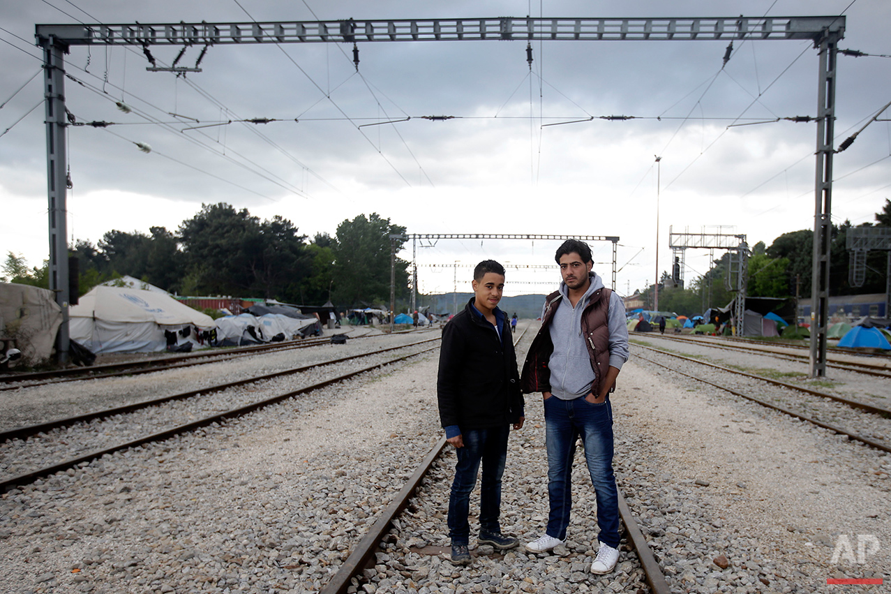 Syrians Mohammed Nur Sermini, left, and Mohammed Samir pose for a portrait on the tracks of a rail way station which was turned into a makeshift camp crowded by migrants and refugees at the northern Greek border point of Idomeni, Greece, Tuesday, May 3, 2016.  (AP Photo/Gregorio Borgia)