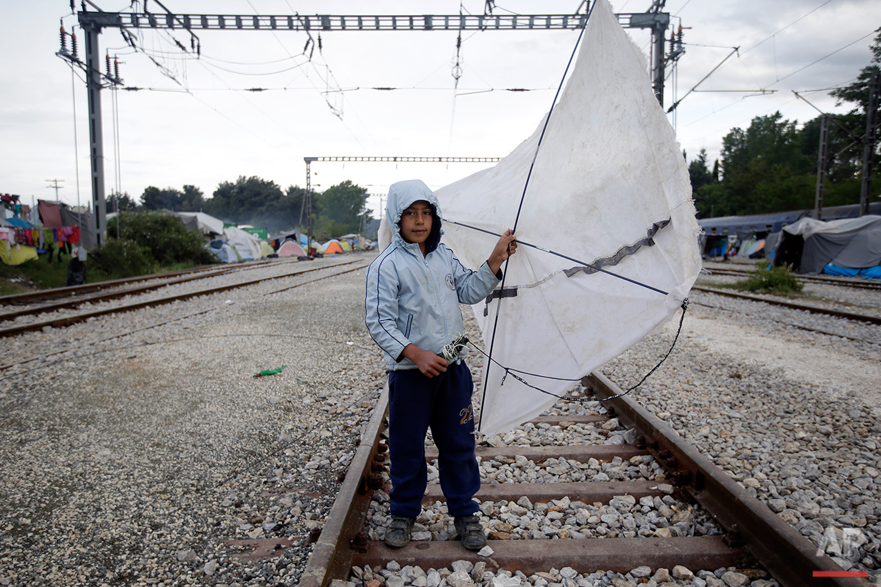 Yesa, 6, from Syria, holds his kite that he made with the sticks of a broken tent as he poses for a portrait on the tracks of a rail way station which was turned into a makeshift camp crowded by migrants and refugees at the northern Greek border point of Idomeni, Greece, Tuesday, May 3, 2016. At Greece's blockaded border with Macedonia, 10,000 people who arrived hoping to start new lives farther west and north in Europe are settling instead into lives in limbo, sleeping in tents in mud and rain as they wait to find out what happens next.  (AP Photo/Gregorio Borgia)