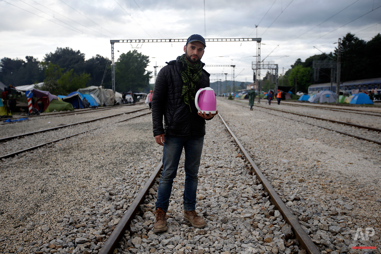 Musab Lalo, from Syria, holds a tea boiler, that he use to sell tea, poses for a portrait on the tracks of a rail way station which was turned into a makeshift camp crowded by migrants and refugees at the northern Greek border point of Idomeni, Greece, Tuesday, May 3, 2016. Many thousands of migrants remain at the Greek border with Macedonia, hoping that the border crossing will reopen, allowing them to move north into central Europe. (AP Photo/Gregorio Borgia)