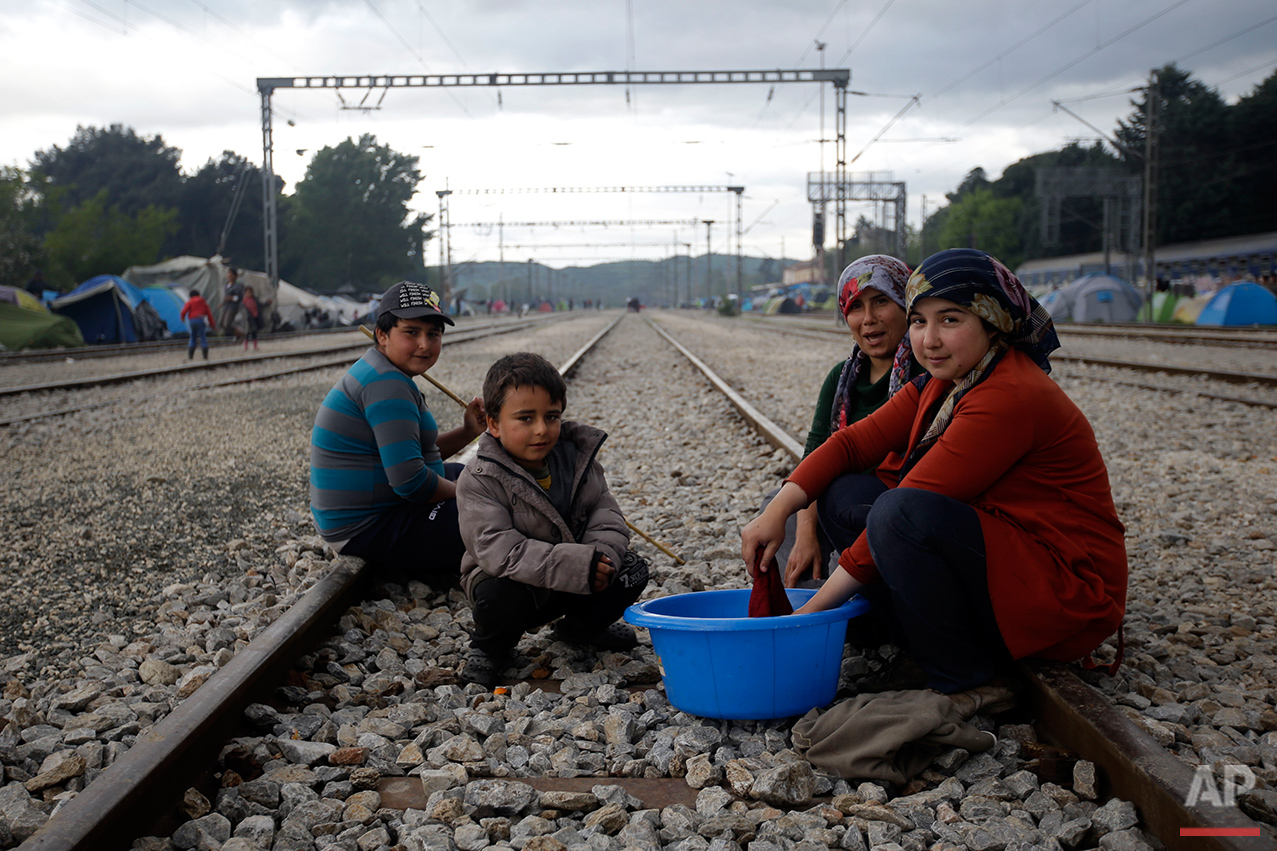 From left, Hames Juma, Mustafa Juma, Fidam Mamu and Susan Ali, all from Syria,  pose for a portrait on the tracks of a rail way station which was turned into a makeshift camp crowded by migrants and refugees at the northern Greek border point of Idomeni, Greece, Tuesday, May 3, 2016. (AP Photo/Gregorio Borgia)
