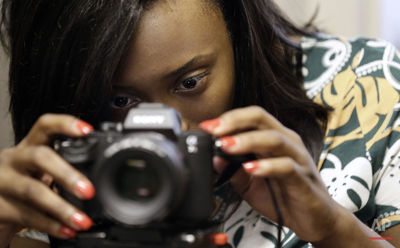 Briana Lawrence, 21, adjusts a camera in a studio at North Carolina Central University in Durham, N.C., on Thursday, July 14, 2016. She was just 7 on Sept. 11, 2001 and the immediate aftermath of the terrorist attacks is the only time she can remember the nation feeling united, even if only by grief. (AP Photo/Gerry Broome)