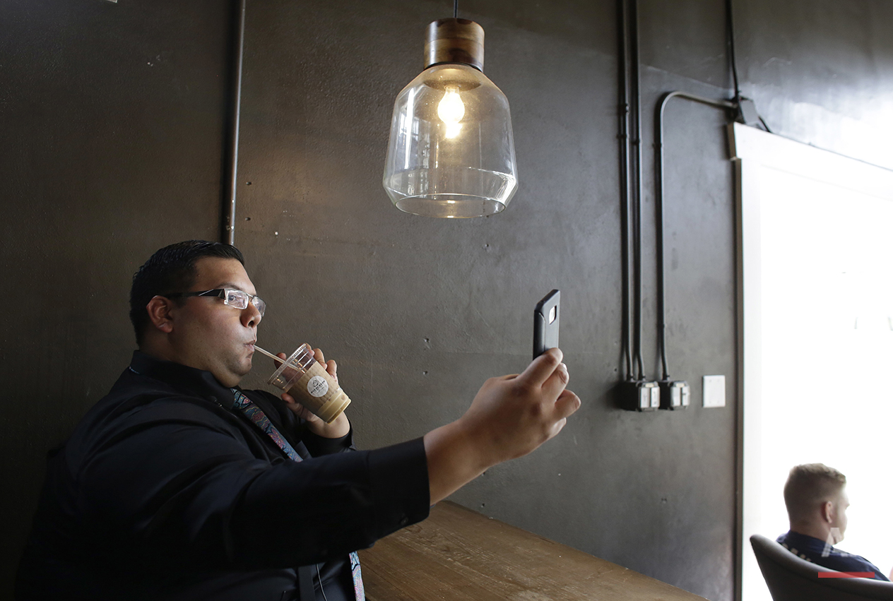 """Anibal David Cabrera, 31, takes a selfie photo during an interview in Tampa, Fla., on Thursday, July 7, 2016. He's backing Trump and prays the candidate keeps promises and boosts the economy. """"That is something my generation has kind of never seen."""" (AP Photo/Lynne Sladky)"""