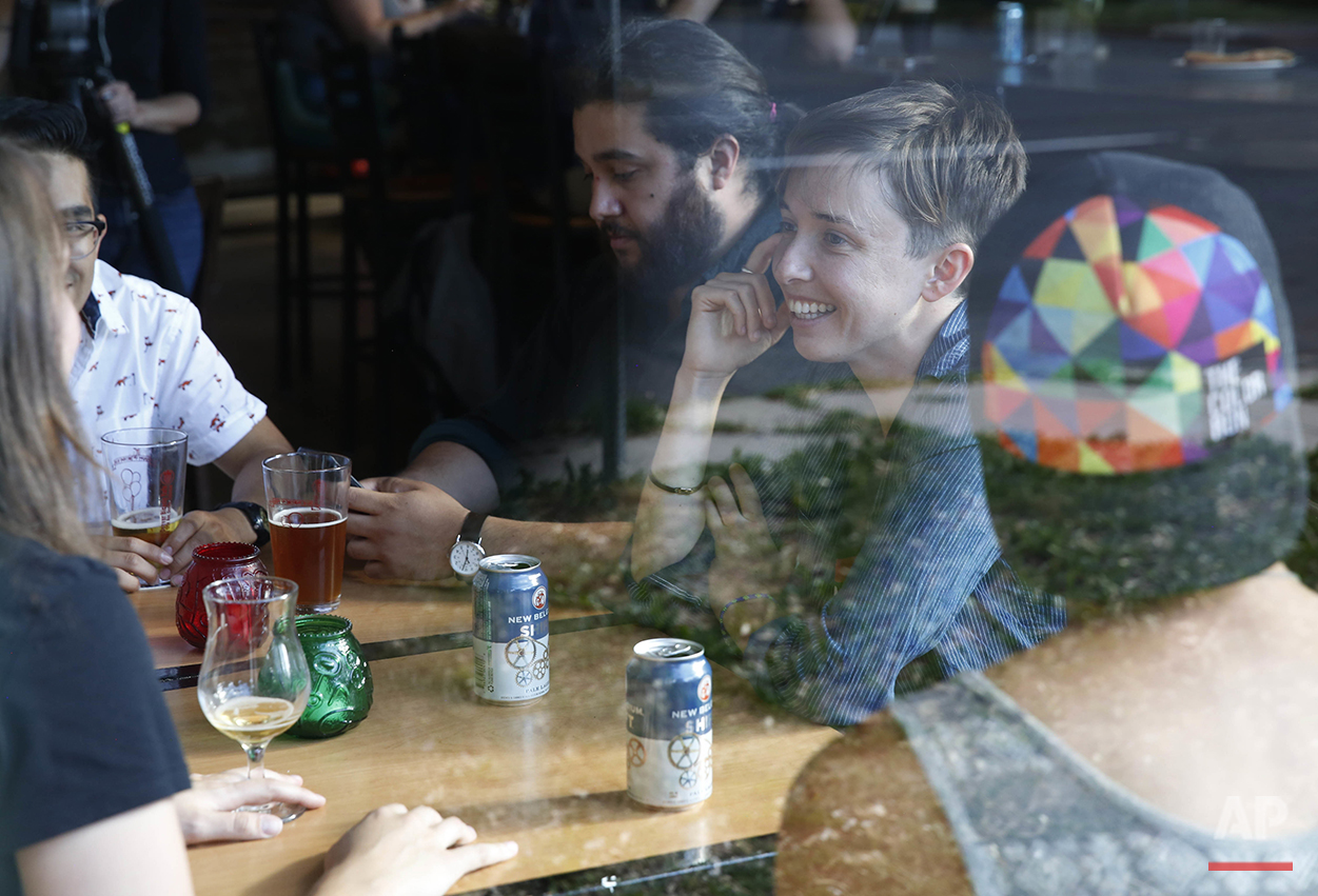 """Diana Downard, 26, a Bernie Sanders supporter who now says she will vote for Hillary Clinton, has drinks with friends at a pub in Denver on July 6, 2016. """"Millennials have been described as apathetic, but they're absolutely not,"""" says Downard """"Millennials have a very nuanced understanding of the political world."""" (AP Photo/Brennan Linsley)"""