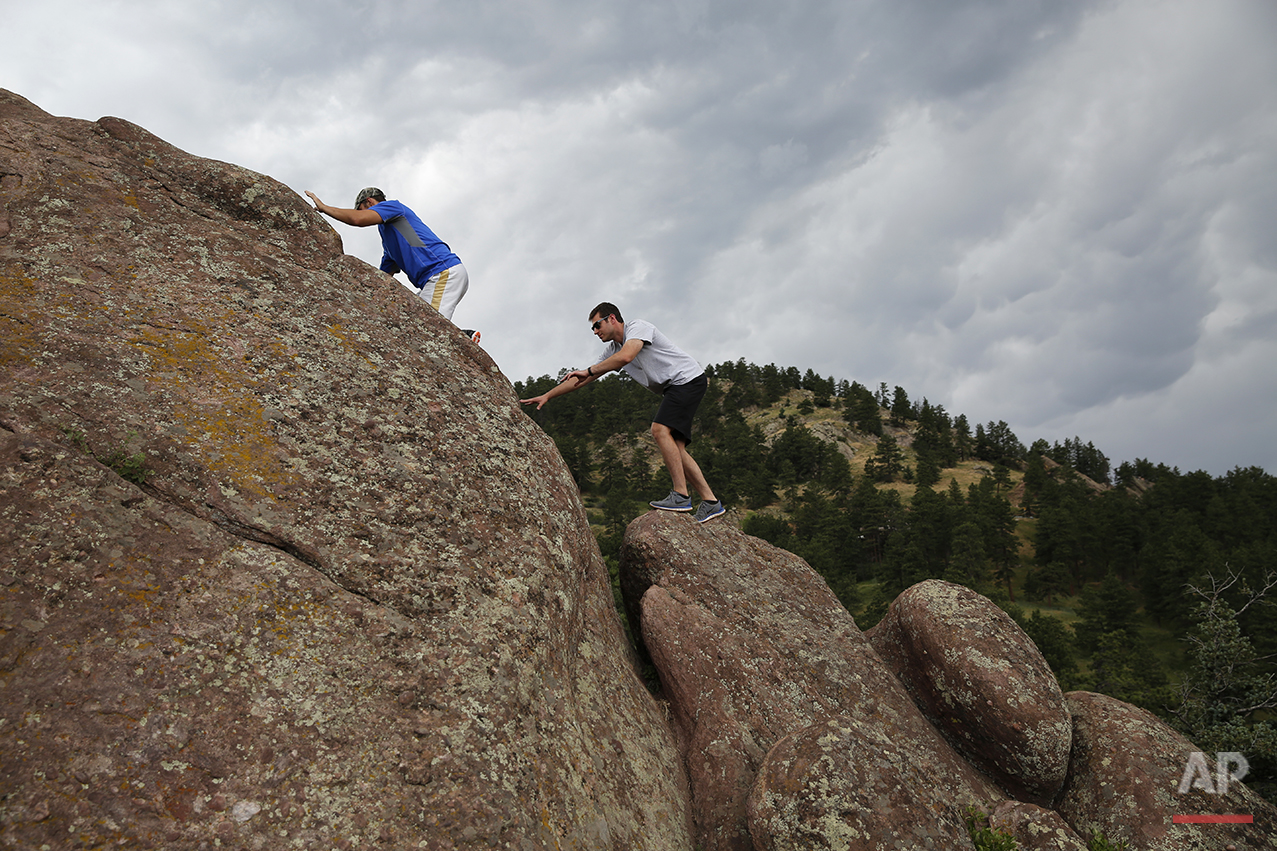 Recent law school graduate and Donald Trump supporter Trip Nistico, 26, right, scales a rock with his friend, Adam Agostini, in the hills above Boulder, Colo., on July 5, 2016. Millennial voters' disdain for traditional party affiliation have made them particularly unpredictable. (AP Photo/Brennan Linsley)
