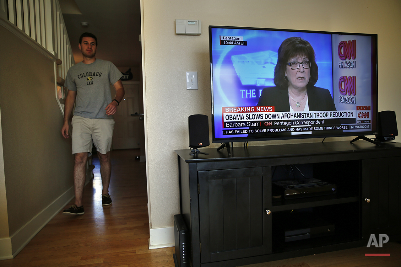 """Recent law school graduate Trip Nistico, 26, walks through his apartment in Boulder, Colo., on July 6, 2016. """"I'm pretty liberal on social issues. I don't really think that _ on a national level _ they're really as important as some of these other issues we've been discussing,"""" he says. He says he's supporting Donald Trump because his preferred candidate, the Libertarian Party's Gary Johnson, isn't likely to crack the polls. (AP Photo/Brennan Linsley)"""