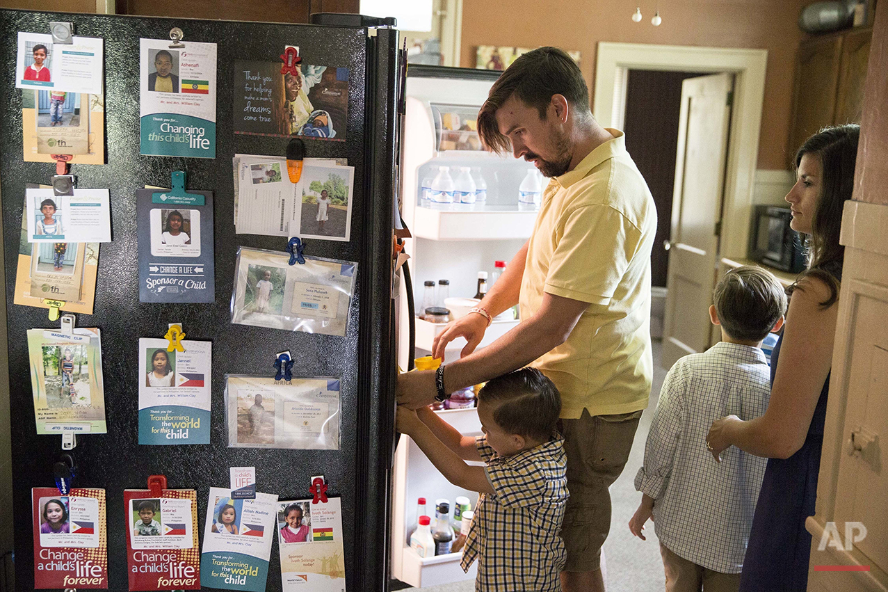 Pictures of children sponsored by Bill Clay, second left, and his wife, Kristi, are displayed on their refrigerator as they prepare breakfast for their children, Ami, left, and Xavier at their home in Ashville, Ohio, on Saturday, July 9, 2016. Kristi Clay opposes same-sex marriage and abortion and names those as her top issues. Yet the 32-year-old school librarian reluctantly leans toward Clinton, because she feels Trump is materialistic and prefers the Democratic views on immigration and poverty. (AP Photo/John Minchillo)