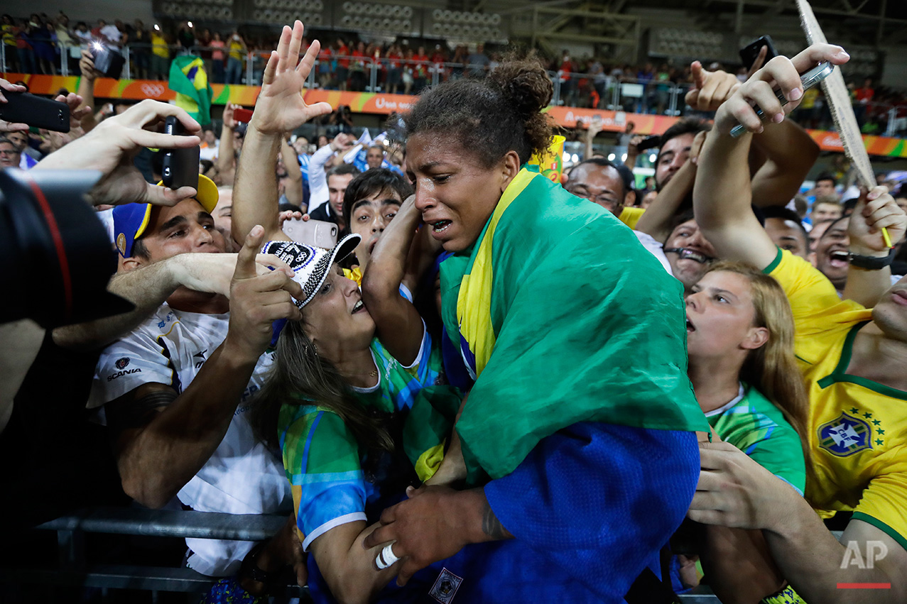 In this Aug. 8, 2016 photo, Brazil's Rafaela Silva, centre, celebrates after winning the gold medal of the women's 57-kg judo competition at the 2016 Summer Olympics in Rio de Janeiro, Brazil. (AP Photo/Markus Schreiber)
