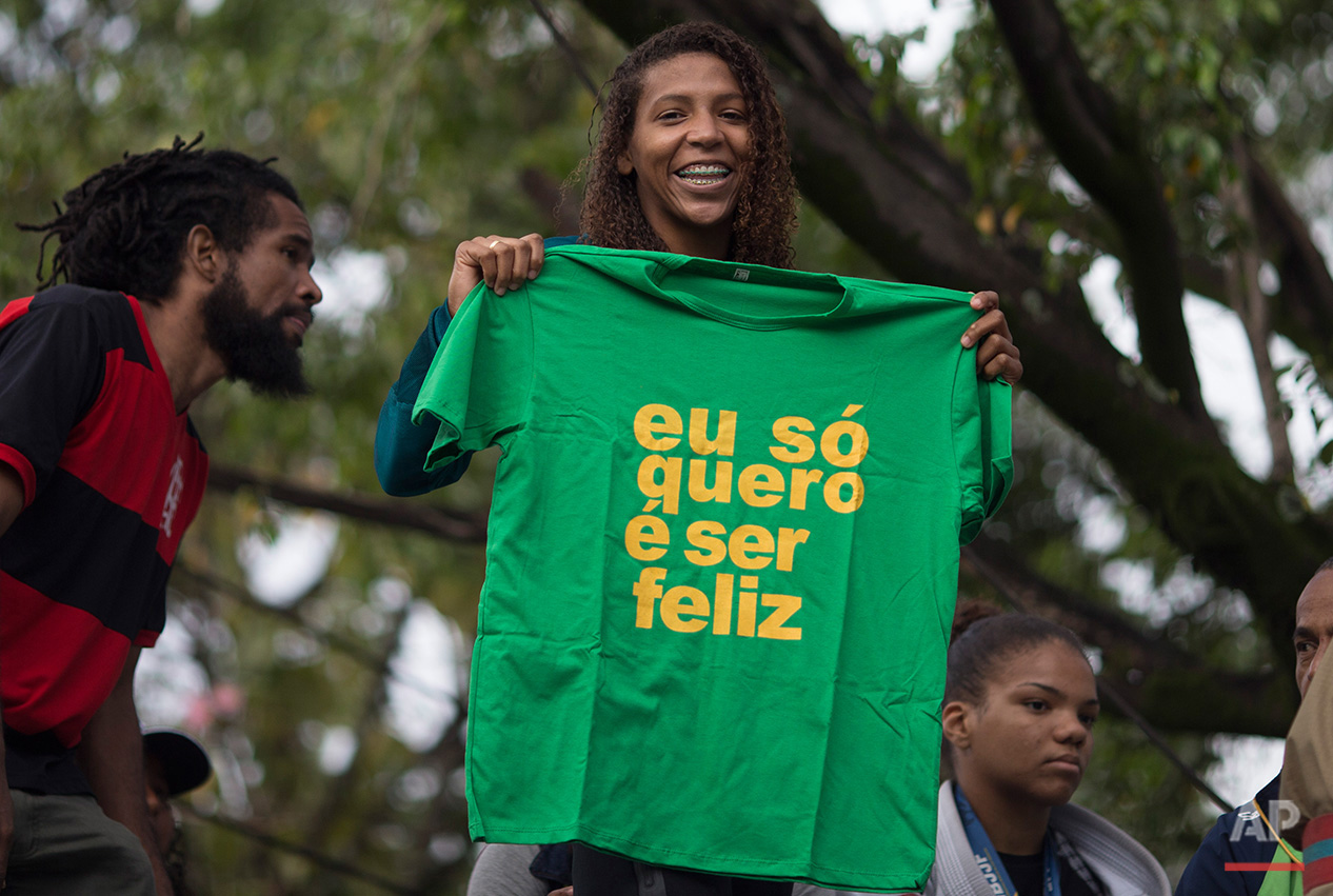 """The Brazilian Judo gold medalist Rafaela Silva holds a T-shirt that reads in Poruguese """" I just want to be happy,"""" as she is given a hero's welcome riding a fire truck into the Cidade de Deus """"City of God"""" slum in Rio de Janeiro, Brazil, Monday, Aug. 22, 2016. Silva who grew up in the violent, poverty stricken slum, won special mention from IOC president Thomas Bach, saying she's an inspiration across the world."""" (AP Photo/Leo Correa)"""