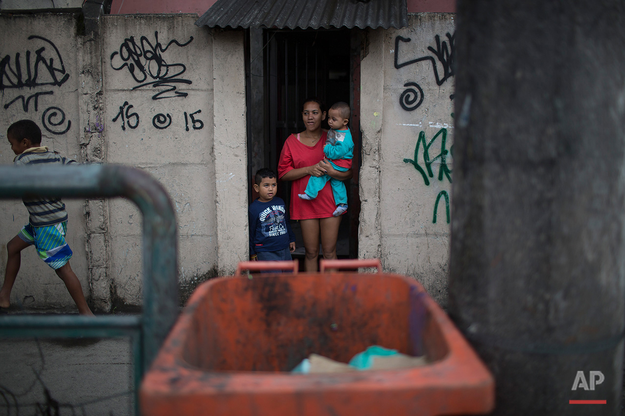 """A woman holding a baby looks from the doorway of her house as Brazilian judo gold medalist Rafaela Silva is given a hero's welcome into the Cidade de Deus """"City of God"""" slum in Rio de Janeiro, Brazil, Monday, Aug. 22, 2016. Silva who grew up in the violent, poverty stricken slum, won special mention from IOC president Thomas Bach, saying she's an inspiration across the world."""" (AP Photo/Leo Correa)"""