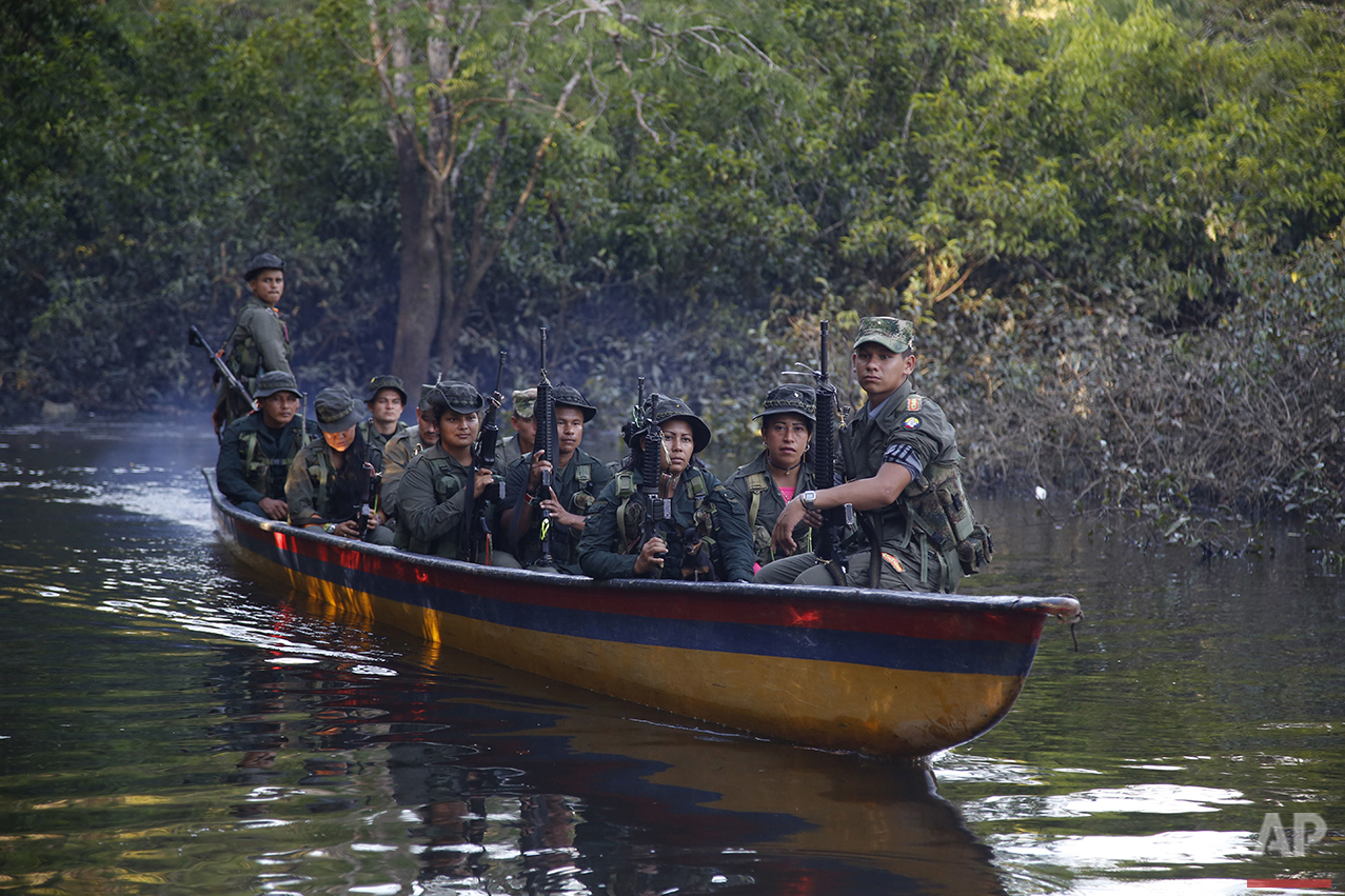 In this Aug. 11, 2016 photo, rebels of the 32nd Front of the Revolutionary Armed Forces of Colombia, or FARC, sit in a boat as they patrol the Mecaya River in the southern jungles of Putumayo, Colombia. (AP Photo/Fernando Vergara)