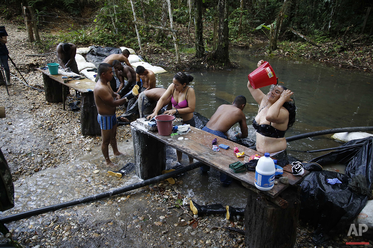 "In this Thursday, Aug. 11, 2016 photo, rebels of the 48th Front of the Revolutionary Armed Forces of Colombia, or FARC, wash their clothes and bathe in a creek near their hidden camp in the southern jungles of Putumayo, Colombia. The rebels were getting ready for a set of intramural soccer games named ""FARC Olympics,"" which were held at the same time as the Rio Games. (AP Photo/Fernando Vergara)"
