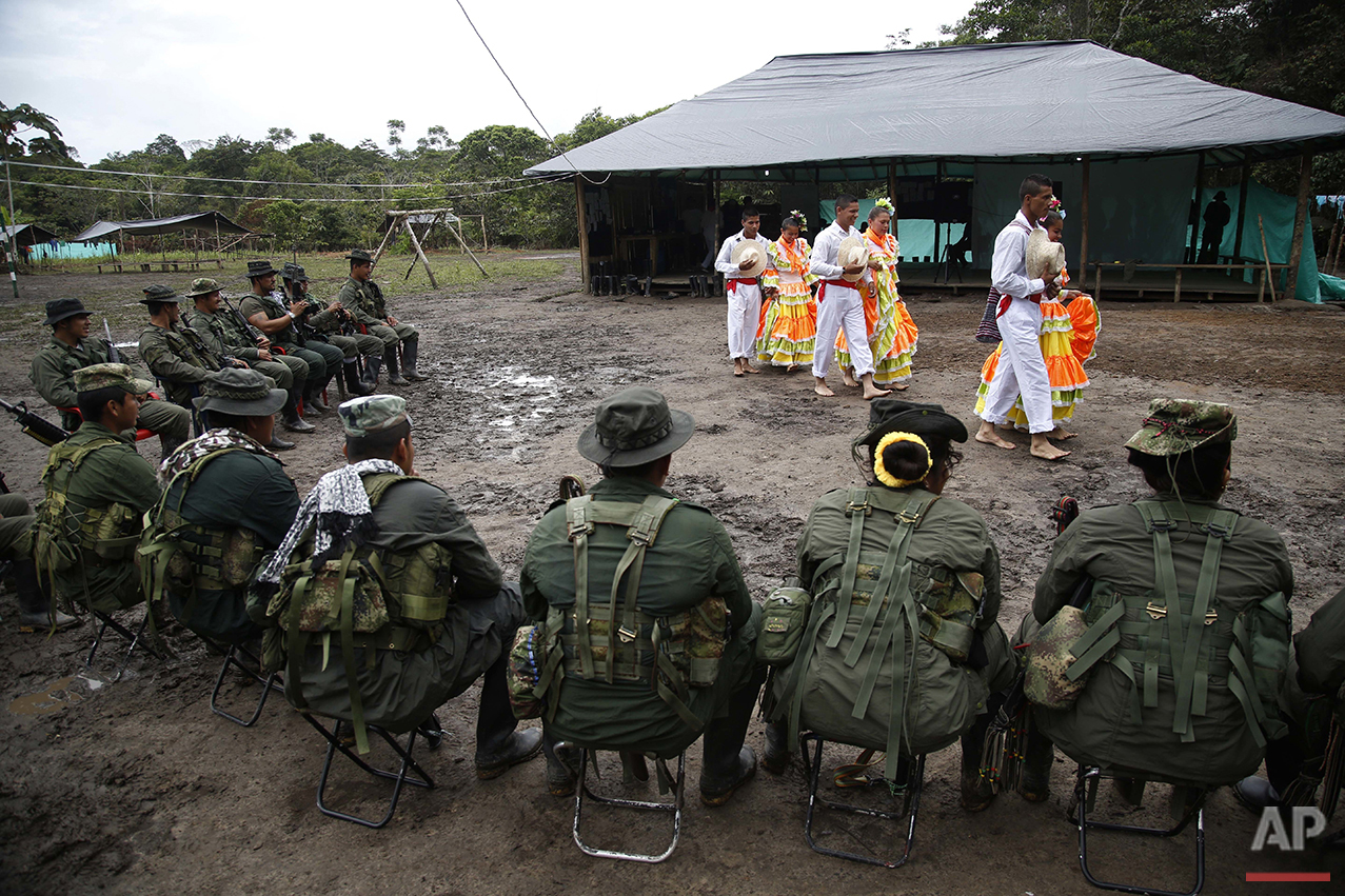 In this Aug. 11, 2016 photo, rebels of the the 32nd Front of the Revolutionary Armed Forces of Colombia perform folk dances in front of their comrades at their camp in the southern jungles of Putumayo, Colombia. The FARC's southern bloc, to which the front belongs, is one of the rebel army's oldest and most belligerent fighting units. (AP Photo/Fernando Vergara)