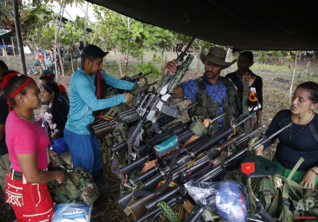 In this Aug. 11, 2016 photo, rebels of the 48th Front of the Revolutionary Armed Forces of Colombia, check-in their weapons before the start of a soccer tournament in the southern jungles of Putumayo, Colombia. The rebels stacked their weapons as revolutionary anthems blasted though loud speakers during the games. (AP Photo/Fernando Vergara)