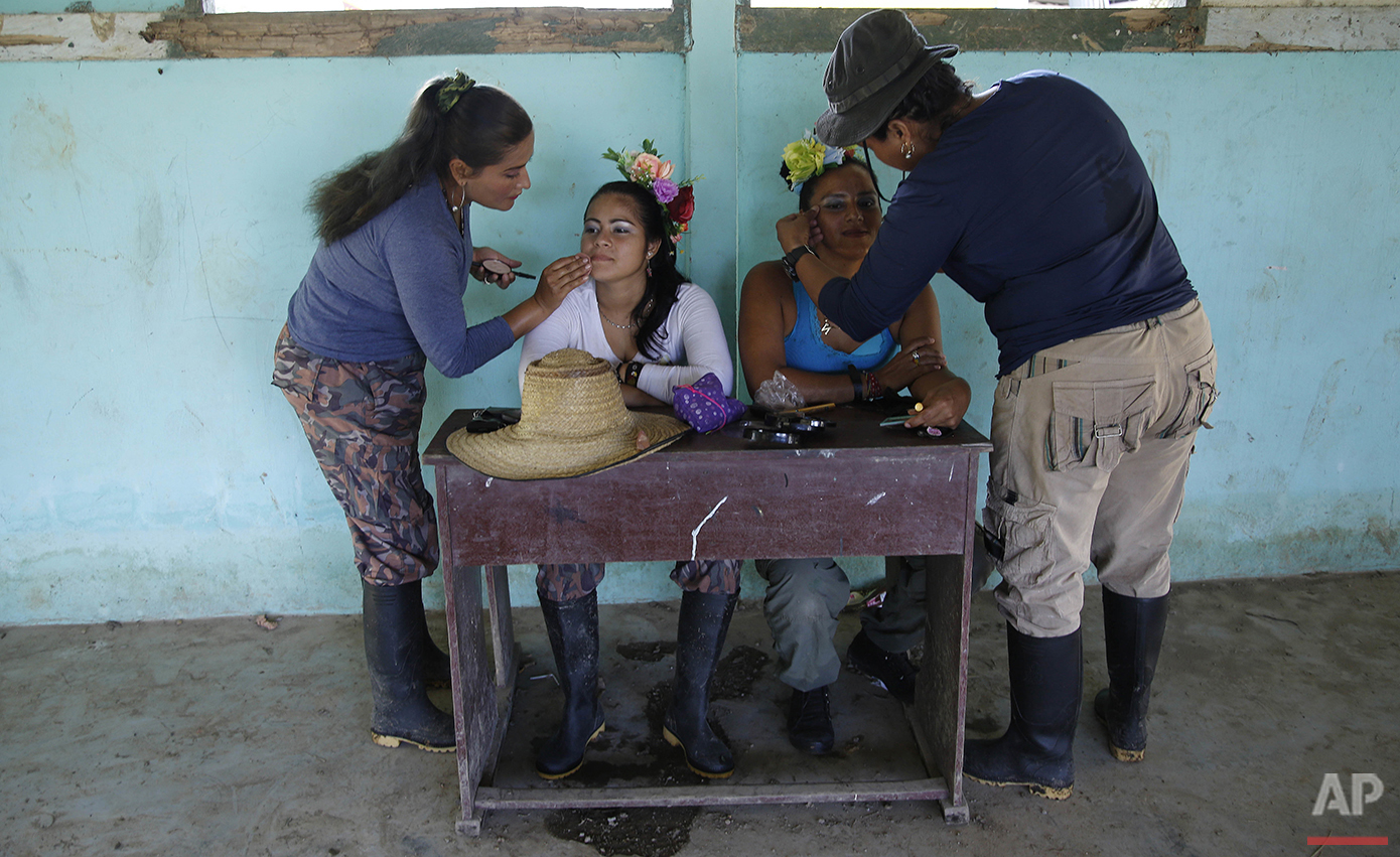 In this Aug. 11, 2016 photo, rebels of the 49th Front of the Revolutionary Armed Forces of Colombia have makeup applied by fellow rebels as they prepare to perform in a dance at their encampment in the southern jungles of Putumayo, Colombia. The women danced a Cumbia, a popular dance that was started by the African population on the Caribbean coast of Colombia. (AP Photo/Fernando Vergara)