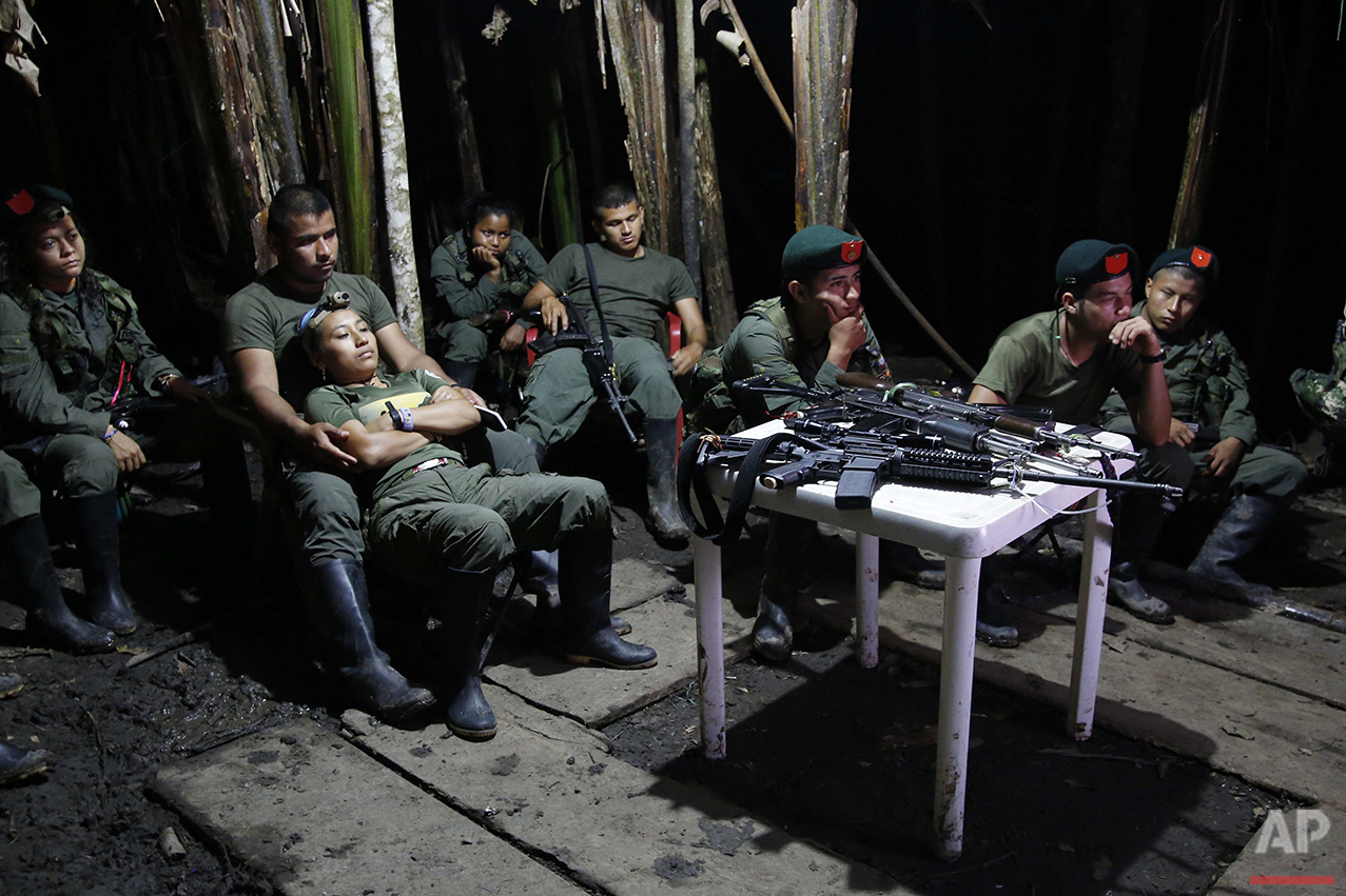In this Aug. 11, 2016 photo, rebels of the 48th Front of the Revolutionary Armed Forces of Colombia watch a nightly newscast on a television at their encampment in the southern jungles of Putumayo, Colombia. The semi-permanent camp is equipped with with refrigerators, satellite TV and even regular access to the internet for commanders. (AP Photo/Fernando Vergara)