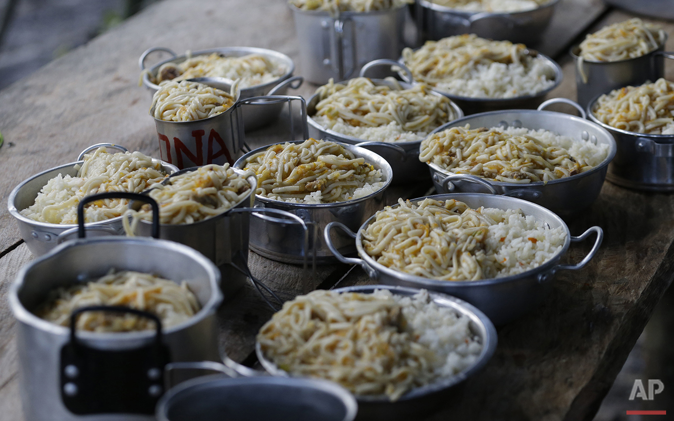 In this Aug. 11, 2016 photo, lunch for the rebels sits ready on a table at the rebel camp of the 48th Front of the Revolutionary Armed Forces of Colombia in the southern jungles of Putumayo, Colombia. The meals consist of dishes filled to the brim with noodles and rice. (AP Photo/Fernando Vergara)