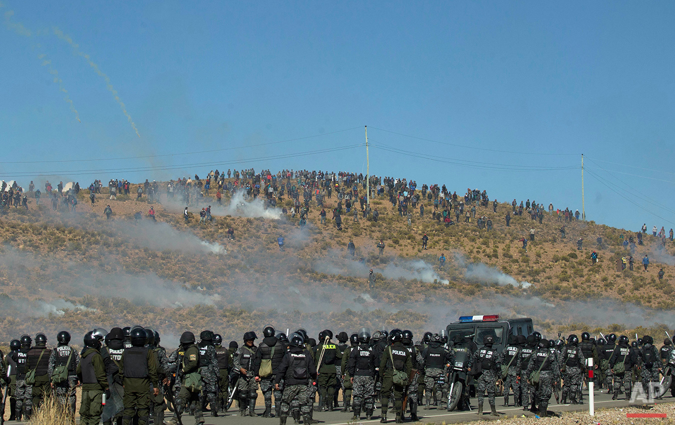 Independent miners, above, clash with the police as they run from clouds of tear gas during protests in Panduro, Bolivia, Thursday, Aug. 25, 2016. Thousands of miners continued their roadblock protests which precipitated the clashes as the police attempted to remove the obstructions. The miners want to be able to associate with private companies but are currently prohibited from doing so. The government argues that if they associate with multinational companies they will no longer be cooperatives. (AP Photo/Juan Karita)