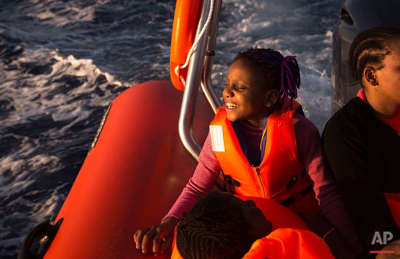 Sira, 9, a migrant from Nigeria, smiles as she rides aboard a boat of the Proactiva Open Arms NGO, after being rescued during an operation in the Mediterranean sea, about 17 miles north of Sabratah, Libya, Saturday, Aug. 20, 2016. (AP Photo/Emilio Morenatti)
