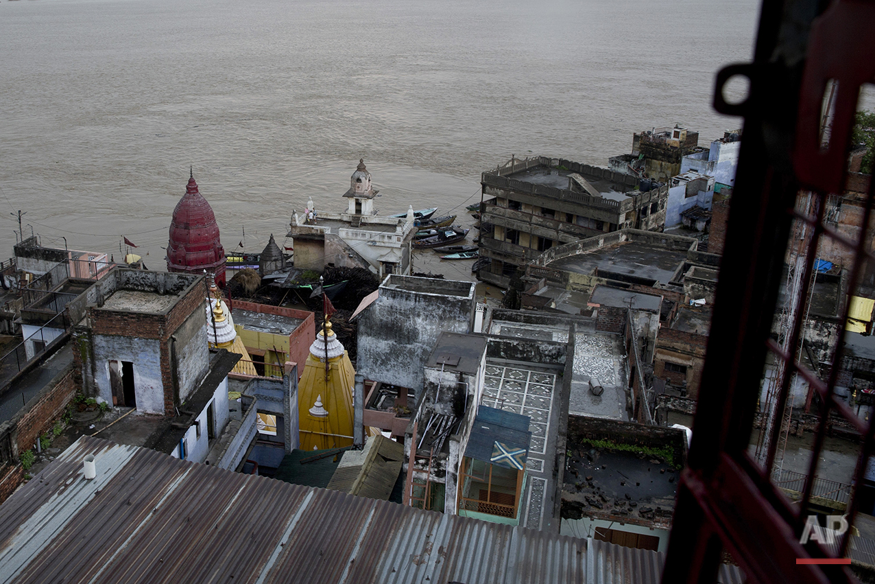 In this Friday, Aug. 26, 2016 photo, the Manikarnika Ghat, center, is submerged by the flood waters in Varanasi, India. As the mighty Ganges River overflowed its banks this past week following heavy monsoon rains, large parts of the Hindu holy town of Varanasi were submerged by floodwaters, keeping away thousands of Hindu devotees. Varanasi is a pilgrim town that Hindus visit to take a dip in the holy Ganges. (AP Photo/Tsering Topgyal) See these photos on  APImages.com