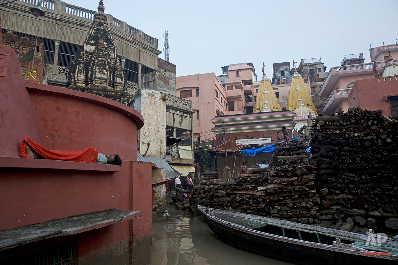 An Indian man sleeps outside a temple as local workers stack woods to be used for funeral pyres at the flooded Manikarnika Ghat in Varanasi, India, Saturday, Aug. 27, 2016. As the mighty Ganges River overflowed its banks this past week following heavy monsoon rains, large parts of the Hindu holy town of Varanasi were submerged by floodwaters, keeping away thousands of Hindu devotees. Varanasi is a pilgrim town that Hindus visit to take a dip in the holy Ganges. (AP Photo/Tsering Topgyal) See these photos on  APImages.com