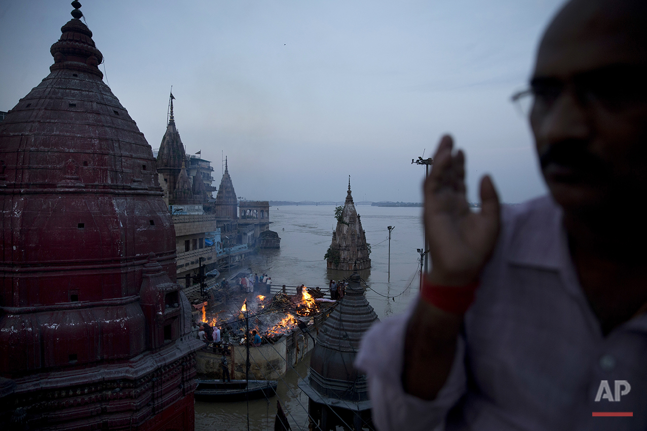 In this Thursday, Aug. 25, 2016 photo, Hindu funerals are performed atop of a Hindu temple at the flooded Manikarnika Ghat in Varanasi, India. As the mighty Ganges River overflowed its banks this past week following heavy monsoon rains, large parts of the Hindu holy town of Varanasi were submerged by floodwaters, keeping away thousands of Hindu devotees. Varanasi is a pilgrim town that Hindus visit to take a dip in the holy Ganges. (AP Photo/Tsering Topgyal) See these photos on  APImages.com