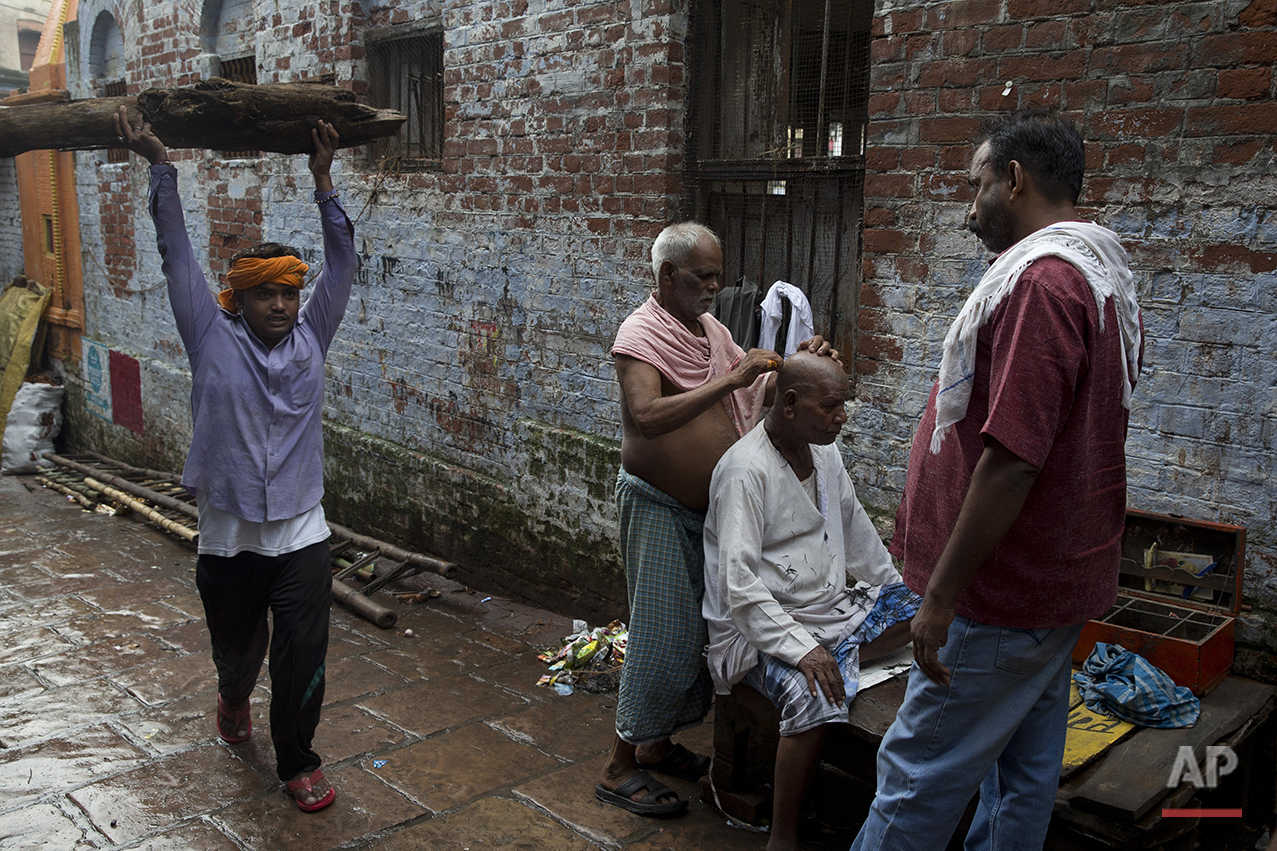 In this Friday, Aug. 26, 2016 photo, a Hindu mourner has his head shaved after attending a funeral service in Varanasi, India.As the mighty Ganges River overflowed its banks this past week following heavy monsoon rains, large parts of the Hindu holy town of Varanasi were submerged by floodwaters, keeping away thousands of Hindu devotees. Varanasi is a pilgrim town that Hindus visit to take a dip in the holy Ganges. (AP Photo/Tsering Topgyal) See these photos on  APImages.com