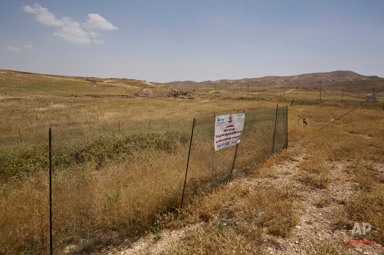 In this May 19, 2016 photo, the site where dozens of Yazidi men were killed in August 2014 is fenced off in Hardan, northern Iraq. An analysis by The Associated Press has found 72 mass graves left behind by Islamic State extremists in Iraq and Syria, and many more are expected to be discovered as the group loses territory. (AP Photo/Maya Alleruzzo)