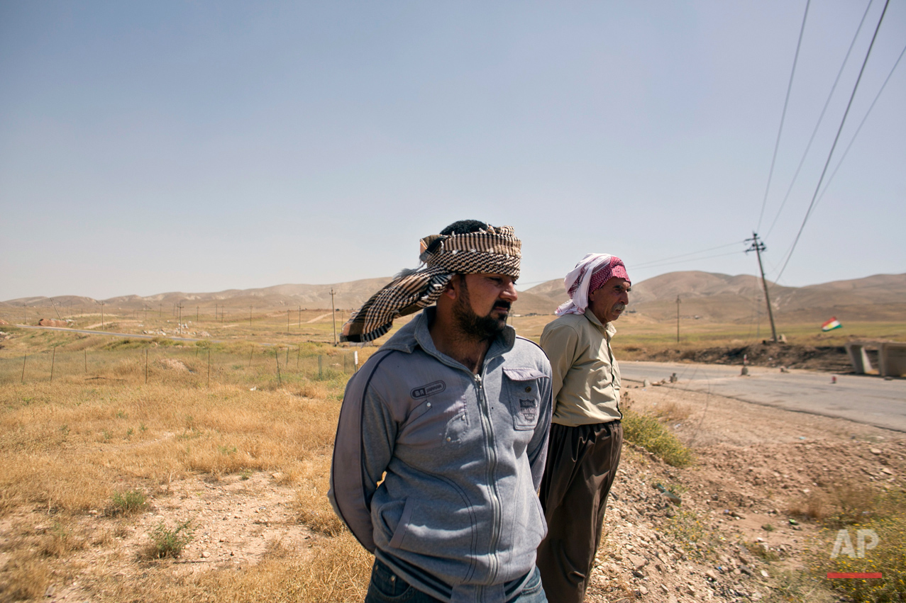 In this May 19, 2016 photo, Arkan Qassim, center, stands at the site where he witnessed the killing dozens of Yazidi men including two sons of Rasho Qassim, right, in August 2014 in Hardan, northern Iraq. Both survivors say they simply want the graves exhumed. (AP Photo/Maya Alleruzzo)